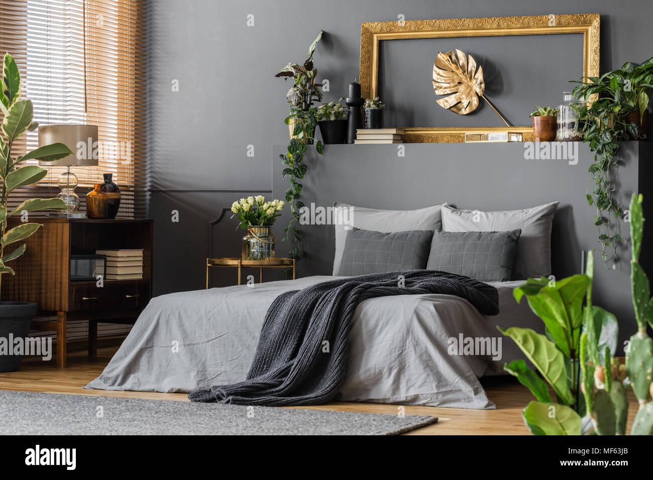 Pan de oro en el bastidor de la pared por encima de la cama con una ...