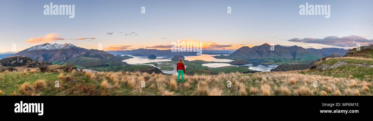 Excursionista con vistas al Lago Wanaka y montañas, pico rocoso, Glendhu Bay, Otago, Southland, Nueva Zelanda Foto de stock