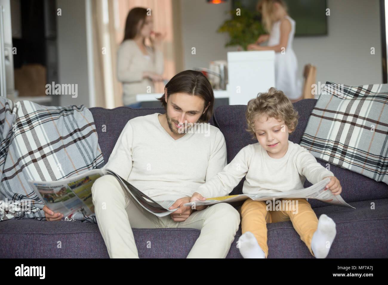 Pequeño hijo simulando la lectura de periódicos sentado en el sofá con fa Imagen De Stock