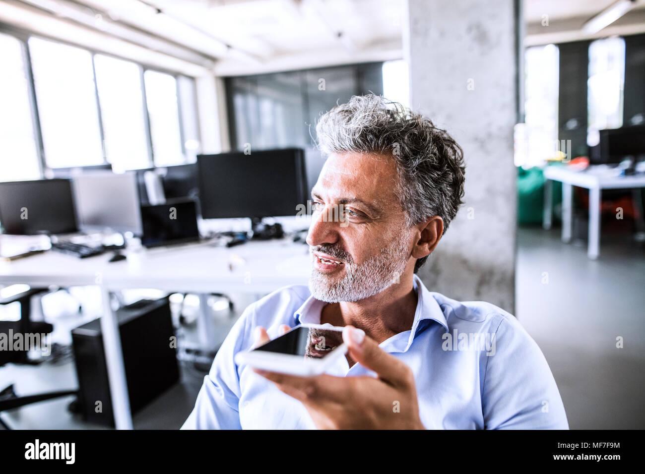 Retrato del empresario maduro con smartphone en Office Imagen De Stock
