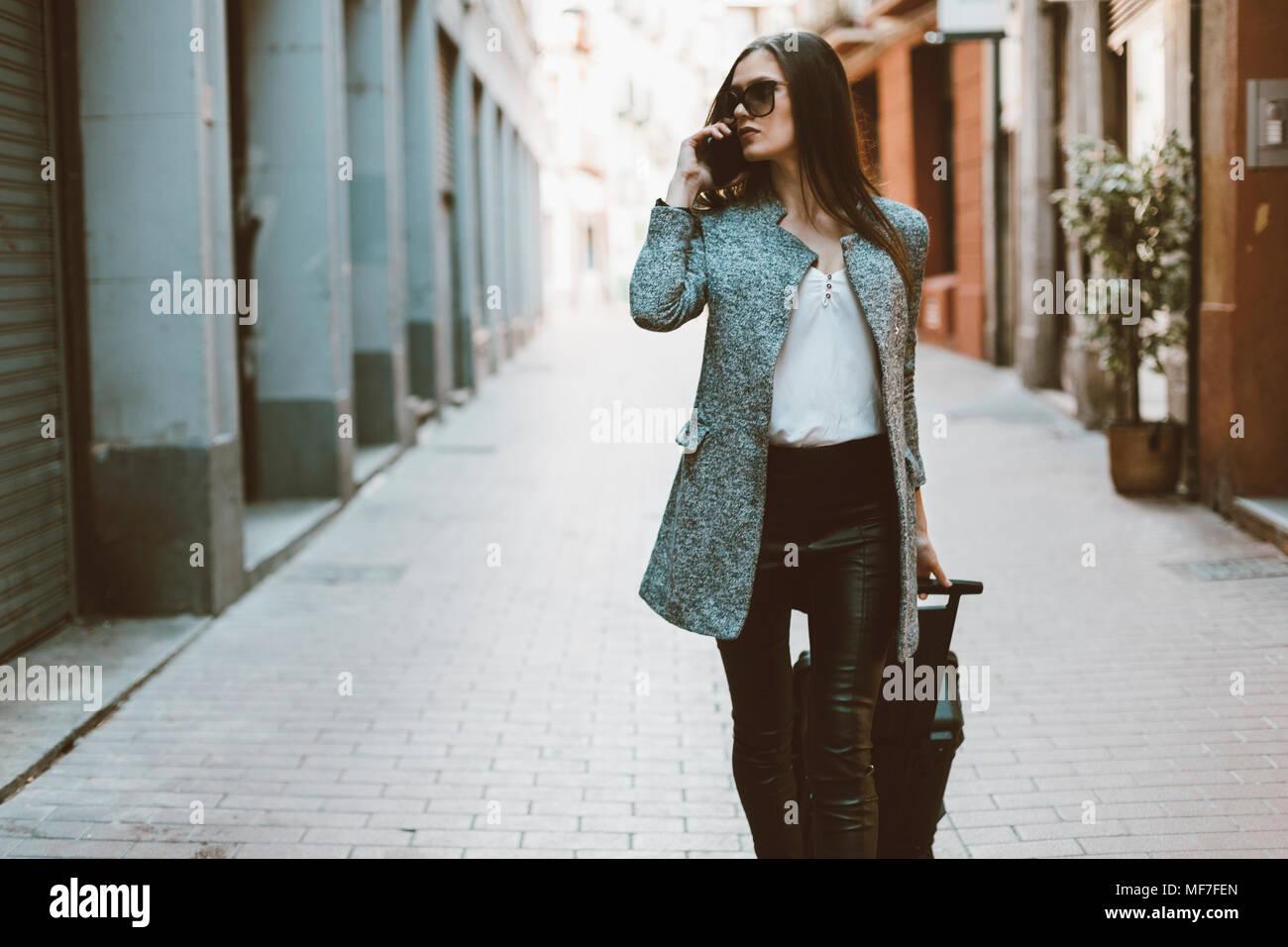 En el teléfono de jóvenes turistas caminando por la calle Imagen De Stock