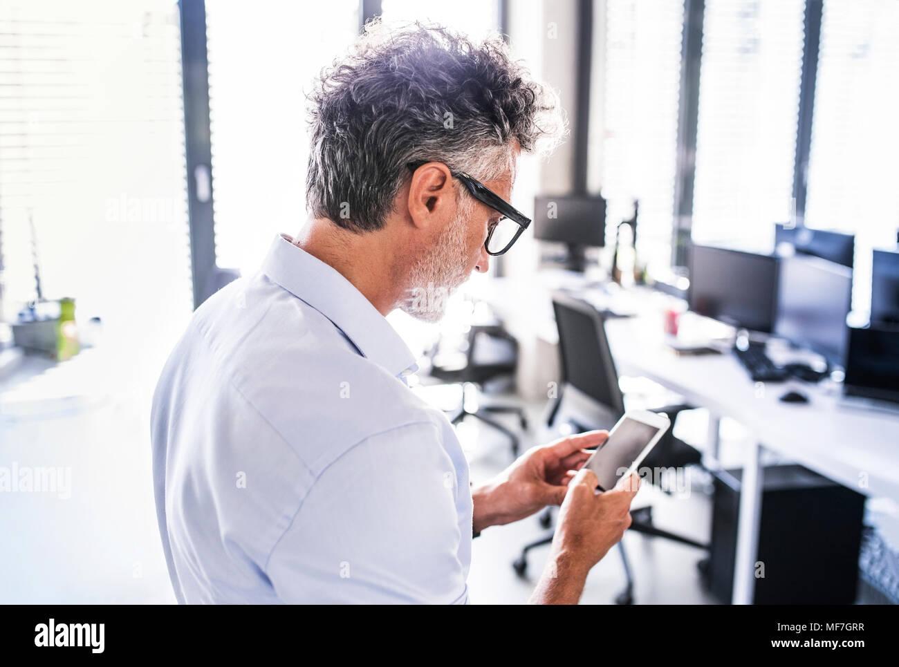 Empresario maduro en la oficina utilizando el smartphone Imagen De Stock
