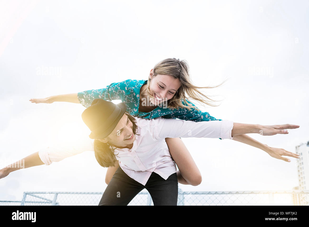 Joven pareja afectuosa divirtiéndonos juntos en la azotea, pretendiendo volar Imagen De Stock