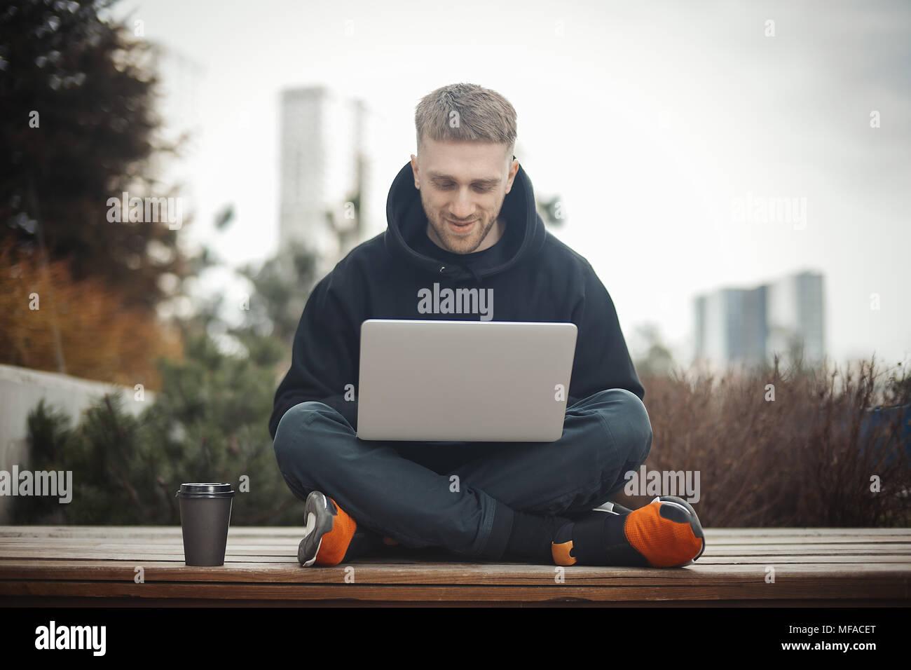 Sonriente joven hombre sujetando el portátil sobre las rodillas. Imagen De Stock