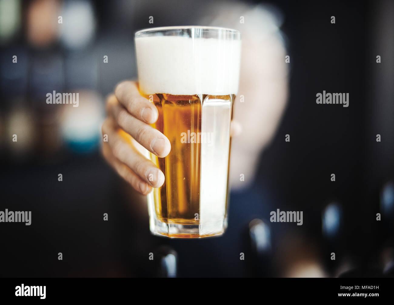 Bartender hombre extiende un vaso de cerveza. Foto de stock