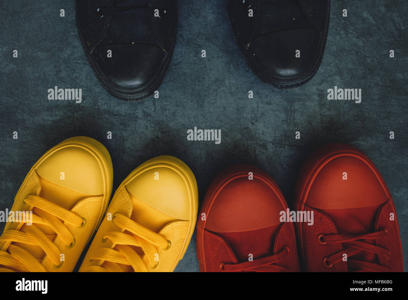 Enfrentamiento juvenil imagen conceptual. Los jóvenes en coloridas sneakers que enfrenta una persona en negro calzado casual. Imagen De Stock