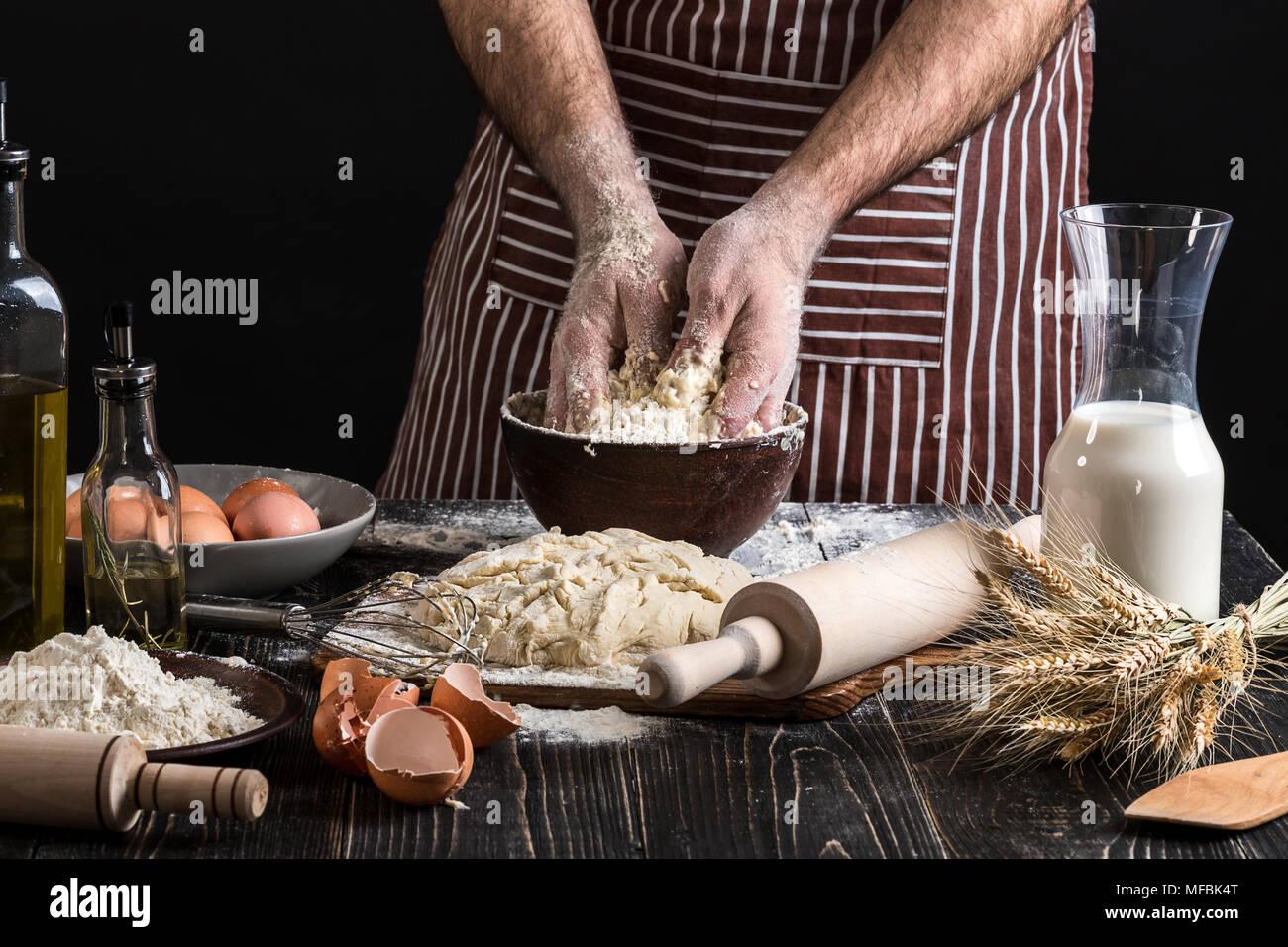 Contra el telón de fondo de las manos del hombre amase la mezcla. Ingredientes para cocinar productos de harina o masa de pan, magdalenas, circulares, masa para pizza . Imagen De Stock