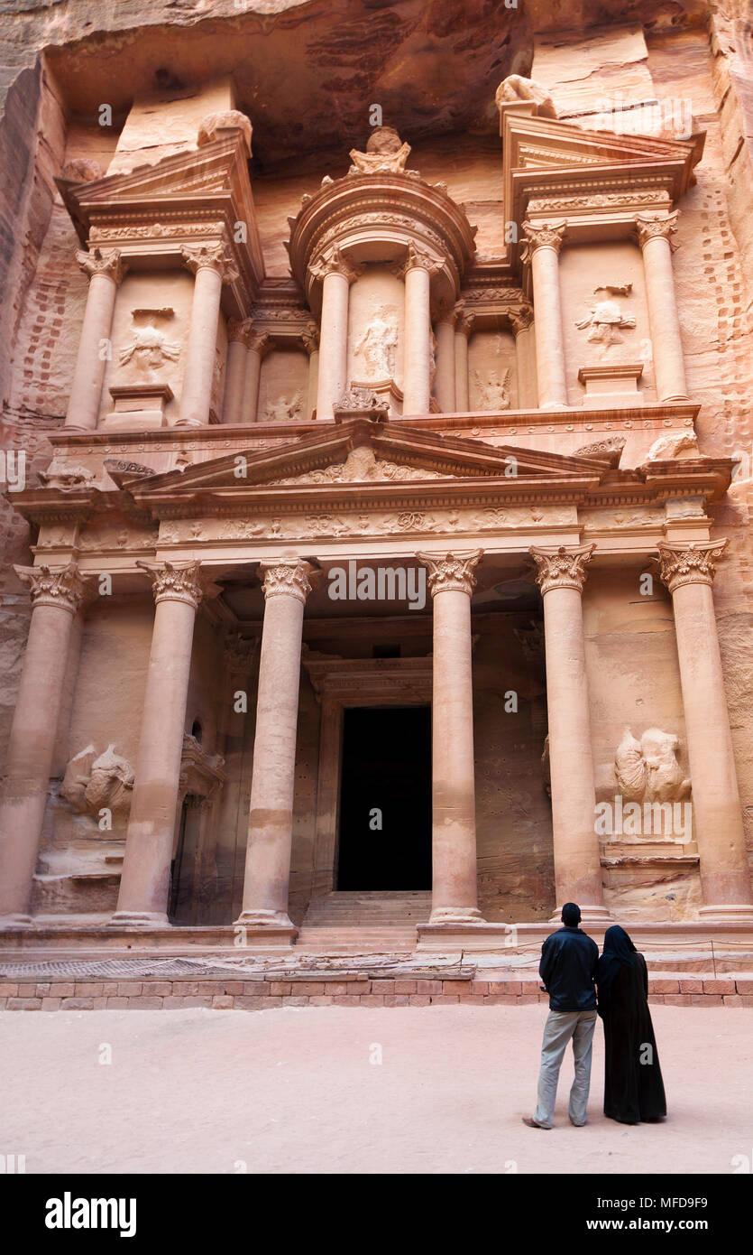 Pareja árabe mirando el templo tallado en la roca de El Hazne, capital del reino nabateo, Petra, Jordania Imagen De Stock