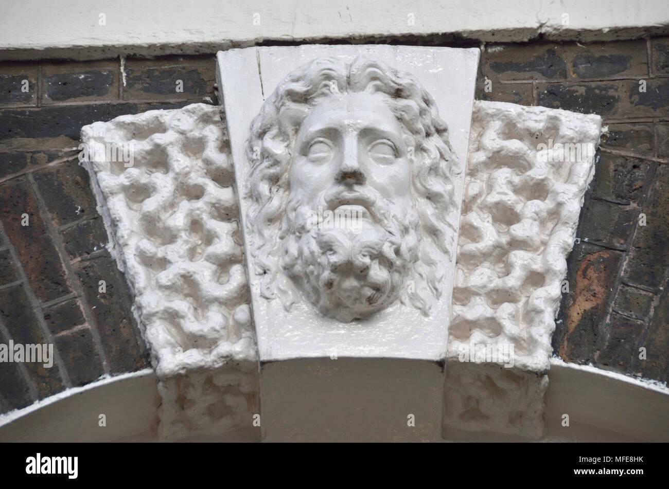 Tallar la piedra ornamental de una cabeza humana por encima de un umbral arch en Bedford Square, Bloomsbury, Londres, Reino Unido. Imagen De Stock