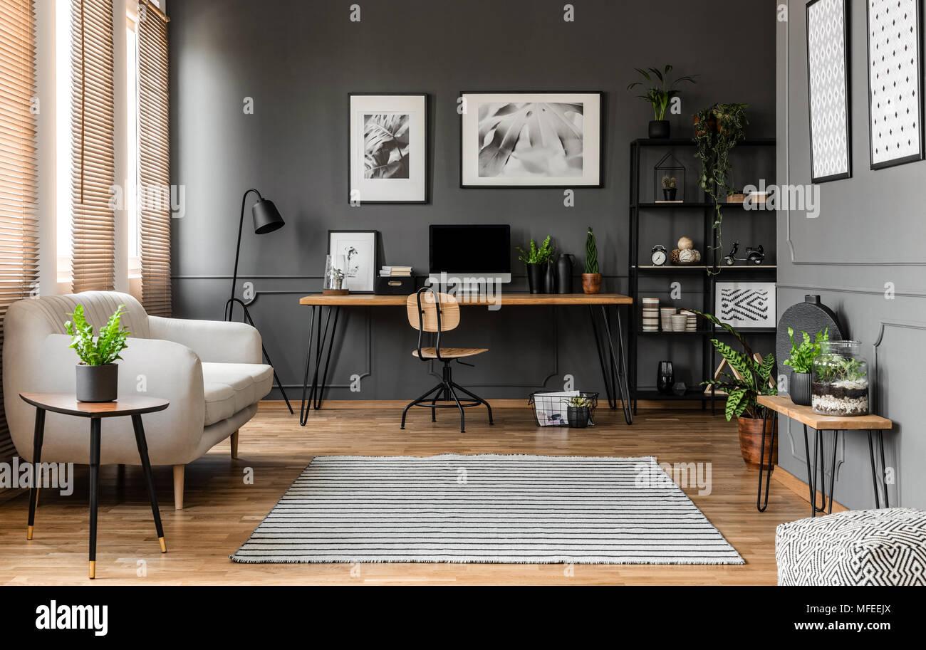 Carteles sobre la pared gris sobre un mostrador de madera con un monitor de ordenador de trabajo moderno con plantas de interior Imagen De Stock
