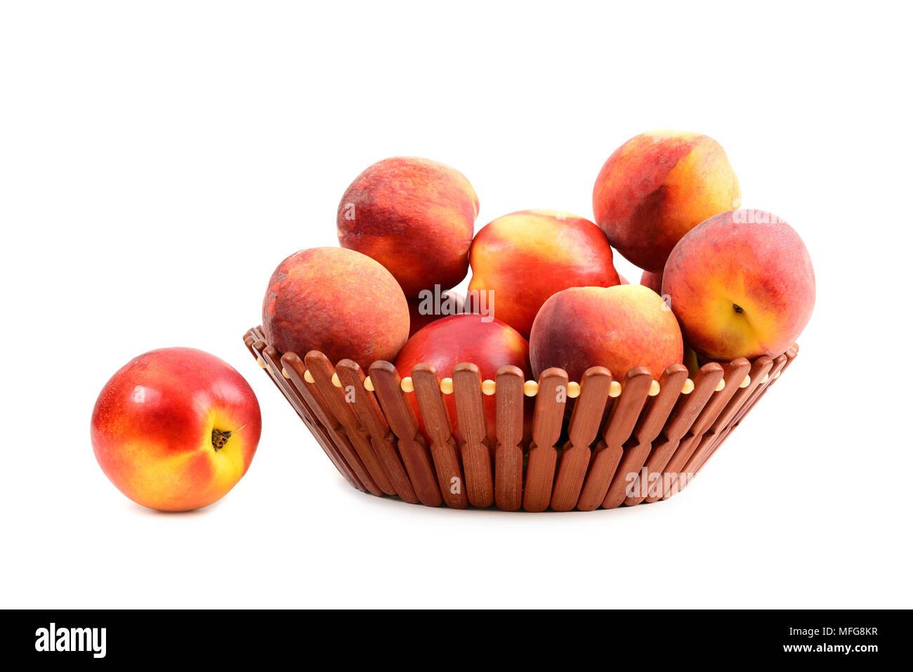 Melocotón fresco en la cesta de frutas sobre fondo blanco aislado Imagen De Stock