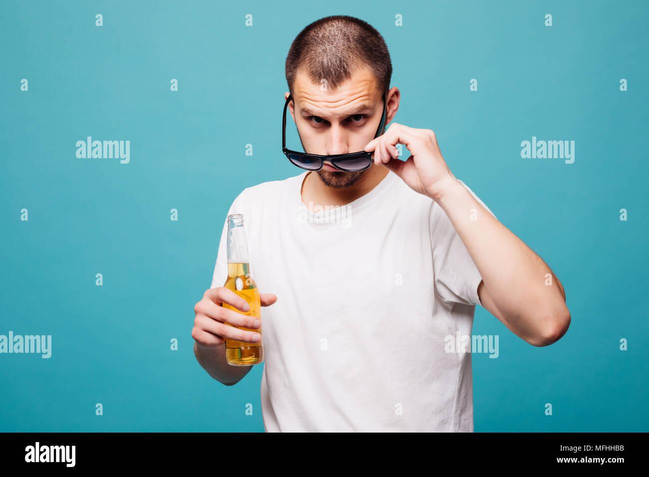Retrato de un feliz verano joven en gafas de sol hombre sujetando las botellas  de cerveza 5095473f7cc7
