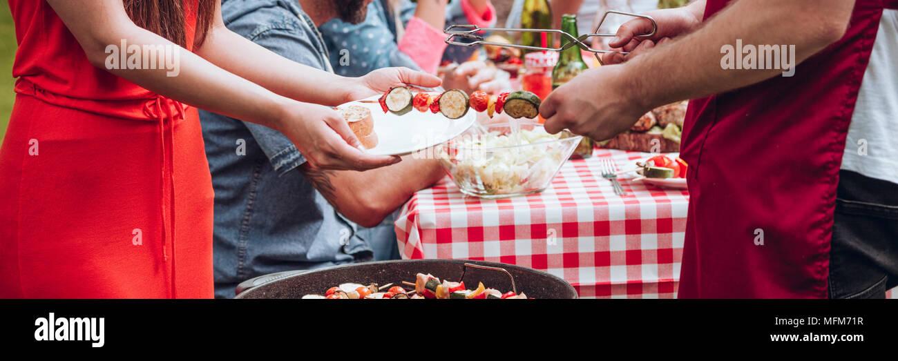Cerca del hombre comparten la comida durante la fiesta de cumpleaños de parrilla Imagen De Stock