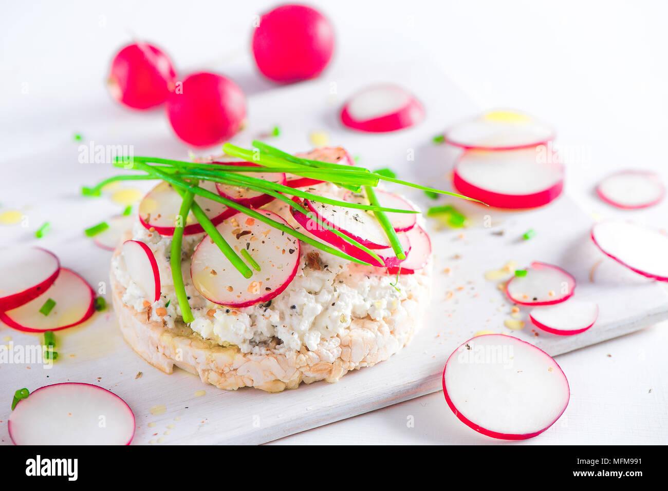Sencillo concepto de desayuno con pan crujiente, rodajas de rábano, el cebollino, la pimienta y el queso cottage. Refrigerio saludable en high key con espacio de copia. Imagen De Stock