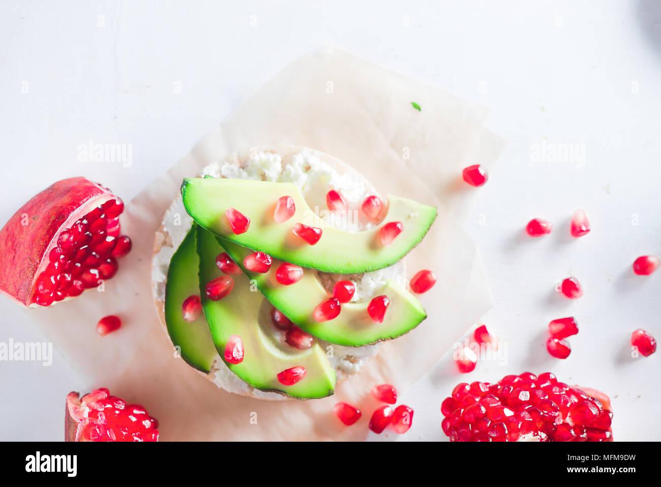 Pan crujiente snack saludable con rodajas de aguacate, suave queso cottage y semillas de granada. Desayuno sencillo concepto sobre un fondo blanco con espacio de copia Imagen De Stock
