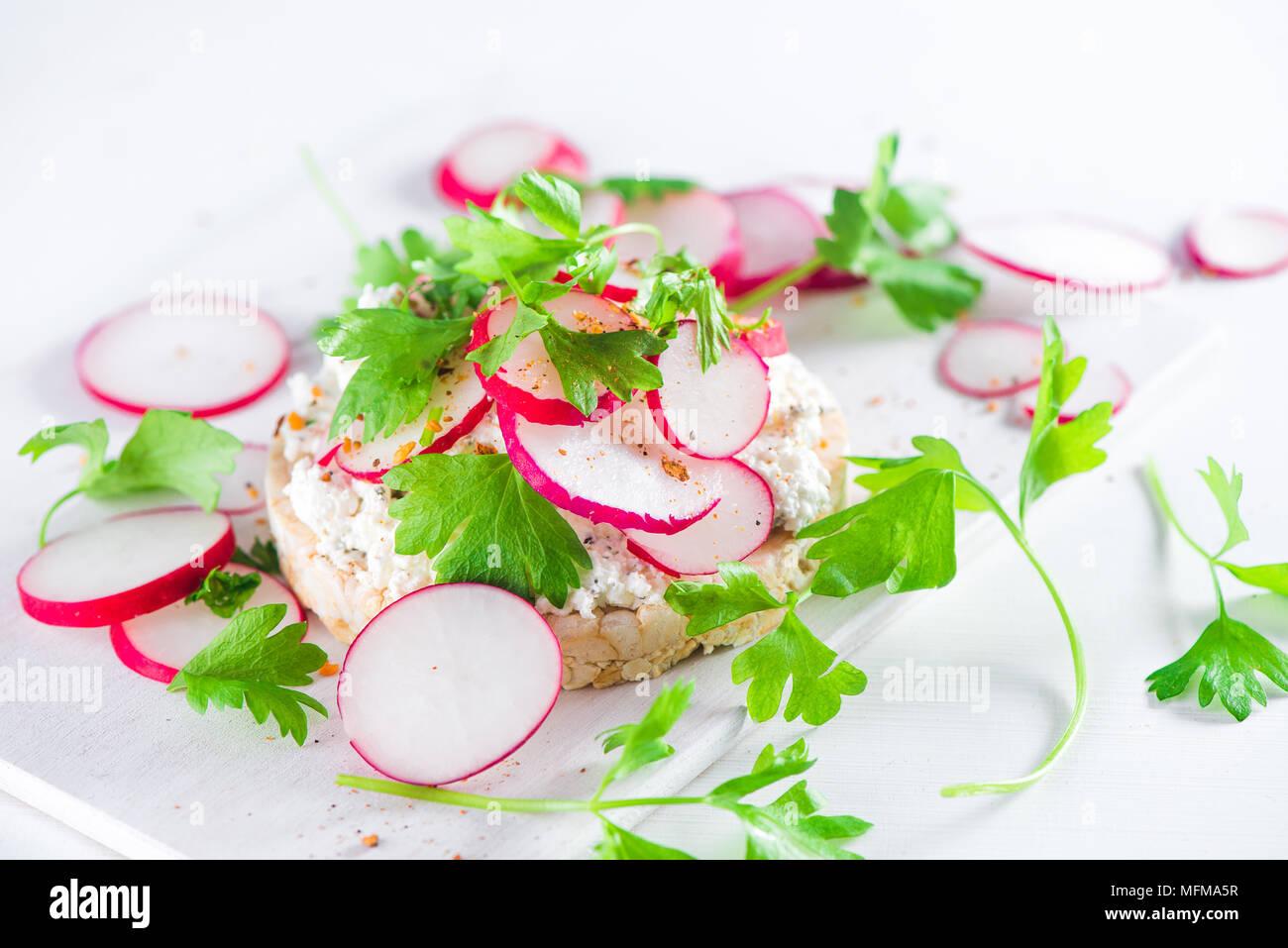 Refrigerio saludable con pan crujiente, rodajas de rábano, perejil, queso cottage y pimienta. Desayuno sencillo concepto en high key con espacio de copia. Imagen De Stock