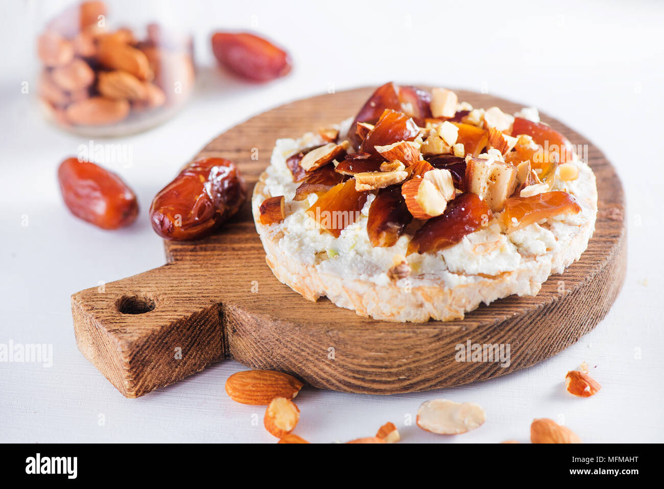 Refrigerio saludable con pan crujiente, fechas suave queso crema, almendras y nueces. Fácil desayuno de cerca en un fondo blanco con espacio de copia. Imagen De Stock