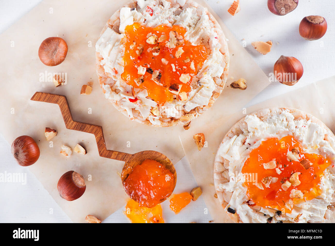 Snack crujiente pan con queso Feta, mermelada de albaricoque y avellana. Fácil desayuno de cerca en un fondo blanco con espacio de copia. Imagen De Stock