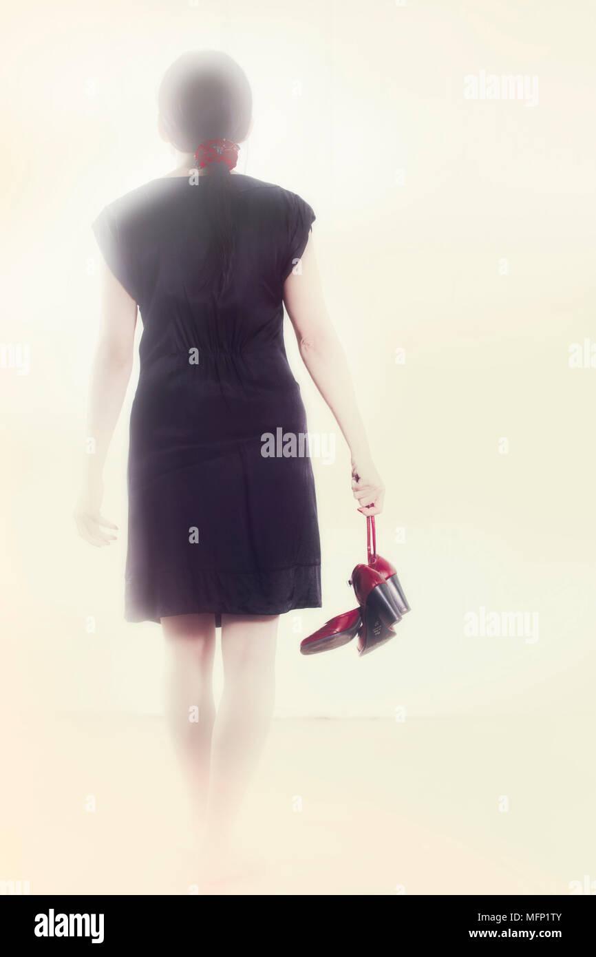 Mujer En Un Vestido Negro Va Con Zapatos Rojos En La Mano
