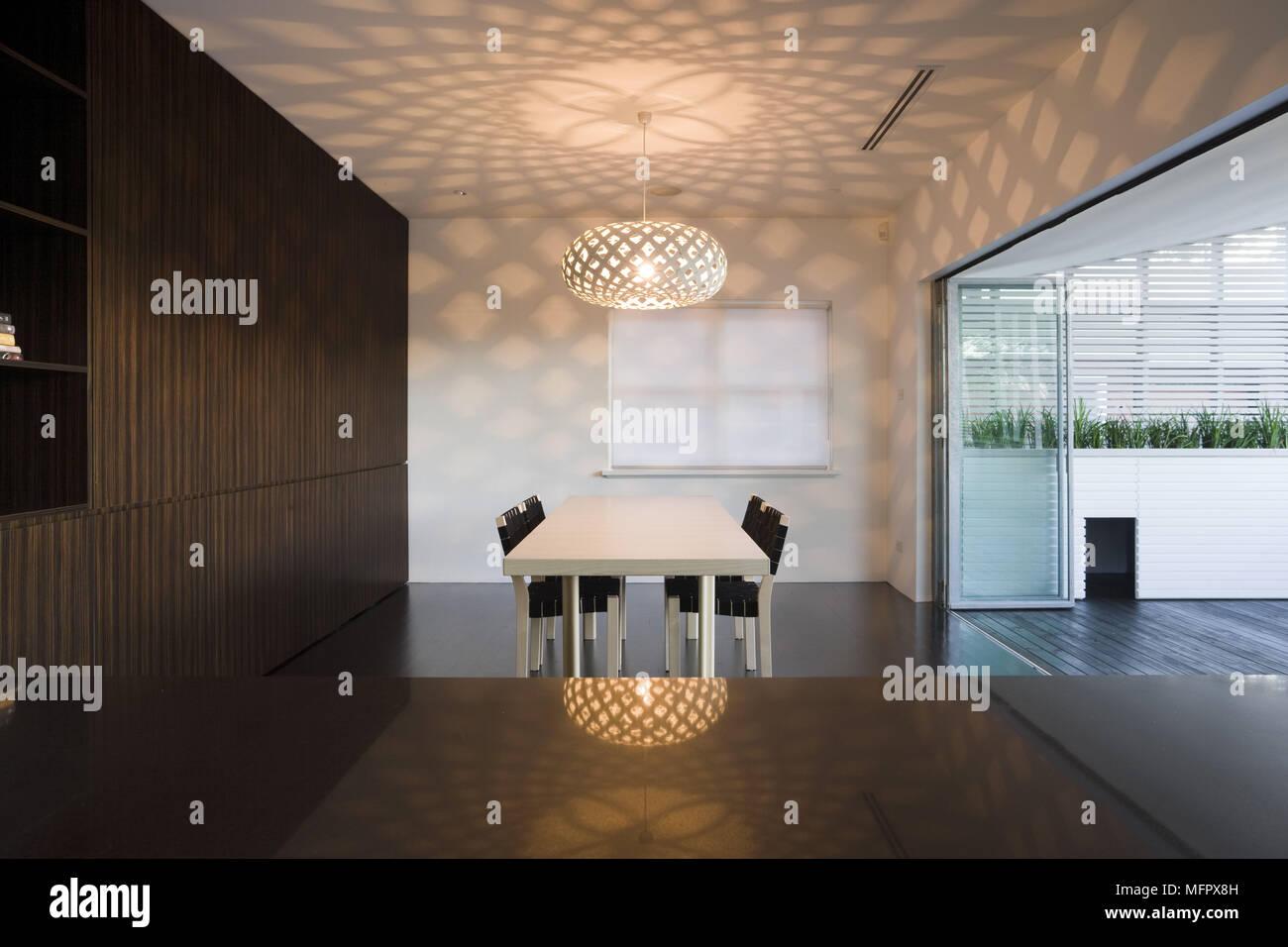 Luz colgante encima de una mesa y sillas de comedor moderno ...