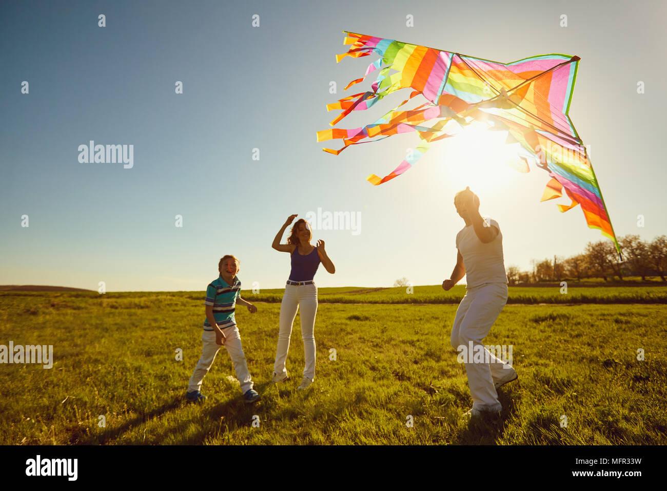 Familia feliz jugando con una cometa en la naturaleza en primavera, verano. Imagen De Stock