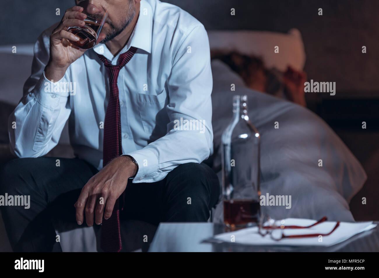 Hombre beber whisky en un palo mientras su mujer está dormido Foto de stock