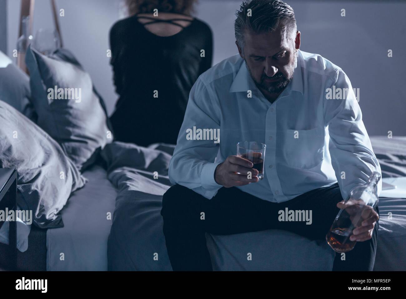 Marido sentado en la cama y en posesión del alcohol mientras tiene una pelea con su esposa Foto de stock