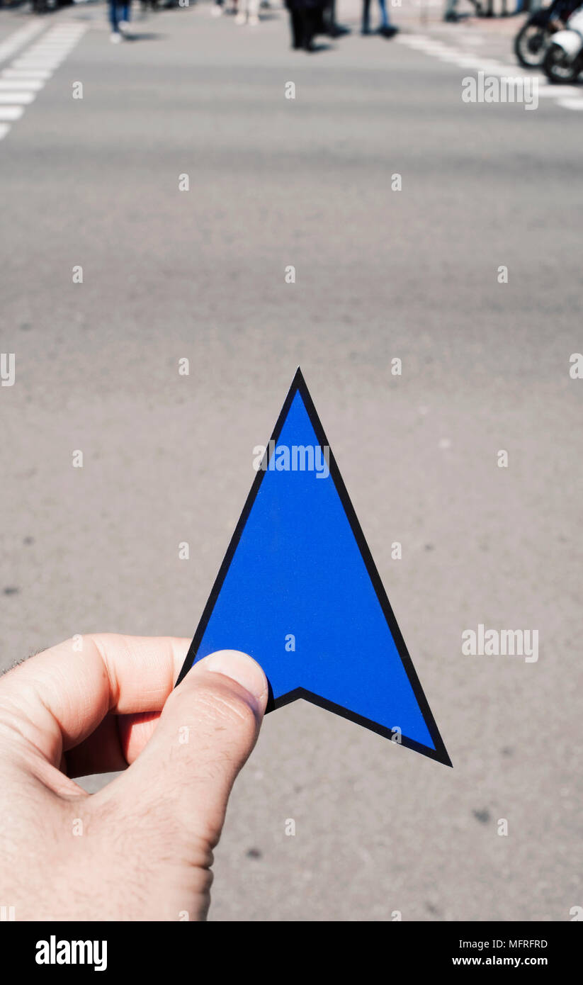 Primer plano de la mano de un joven hombre caucásico con una flecha azul firmar en sus manos en la calle Imagen De Stock