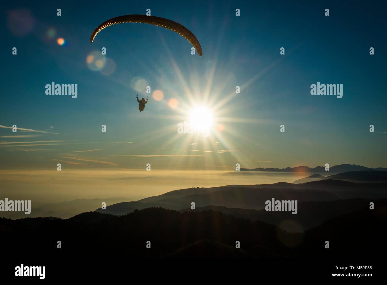Parapente en Monte Grappa, inversión situación meteorológica con la puesta de sol, vista aérea, Bassano, Veneto, Italia Foto de stock