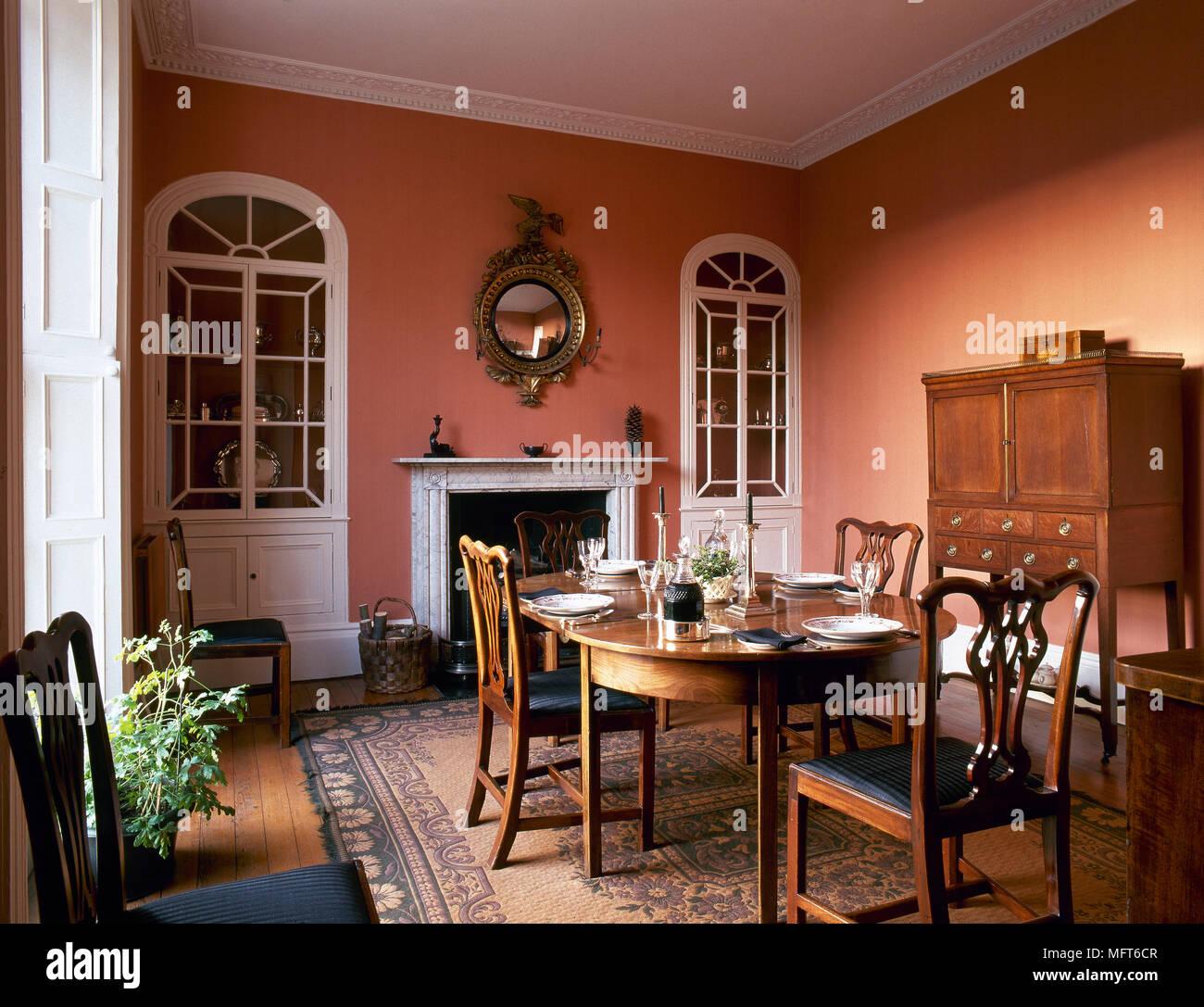Comedor tradicional con paredes de color terracota, madera armario ...