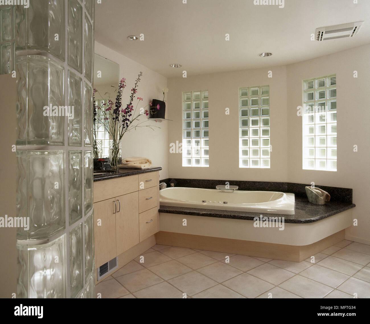 Cuarto de baño con una bañera hundida y pared de ladrillos ...