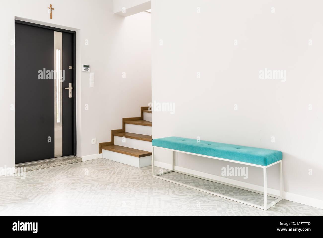 Puerta frontal negro, escaleras y una banqueta tapizados de color turquesa en un hall de entrada interior blanco Foto de stock