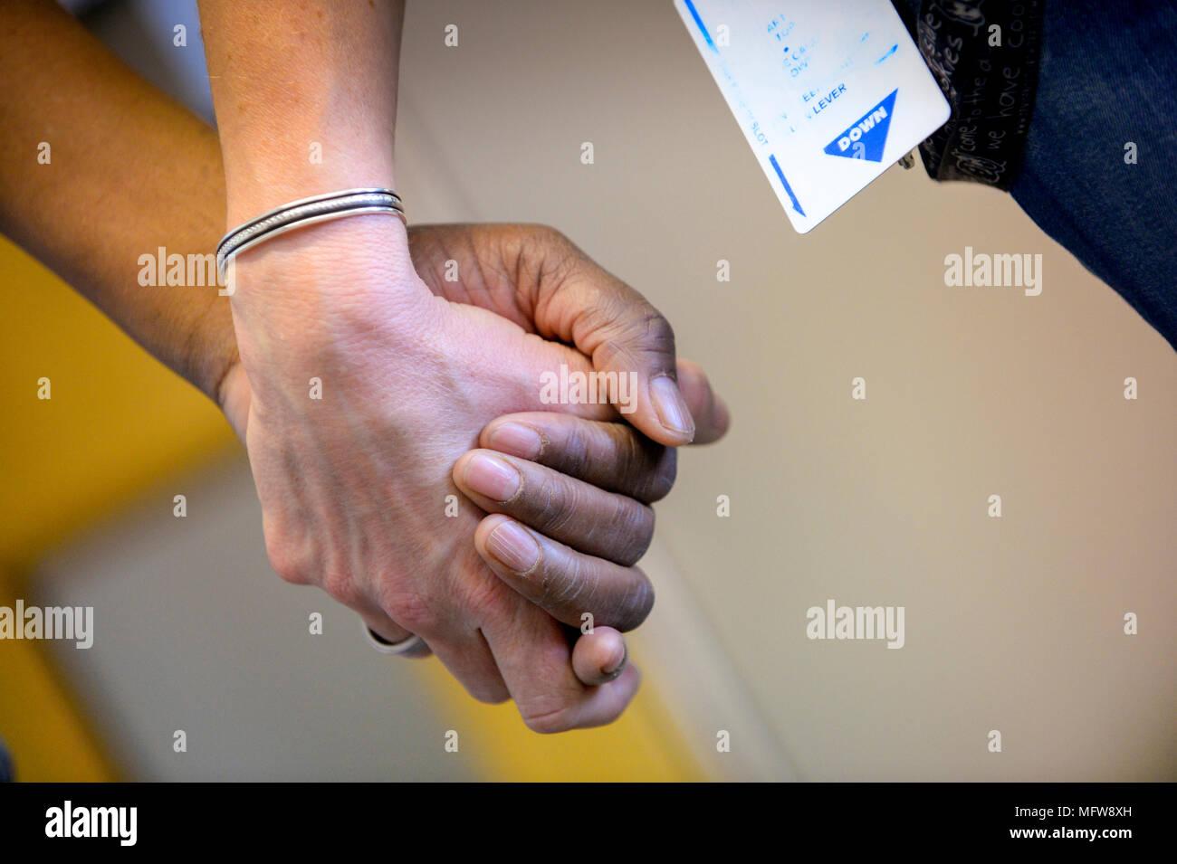 Dos personas cogidas de las manos en un hospital / cuidando el medio ambiente. Imagen De Stock