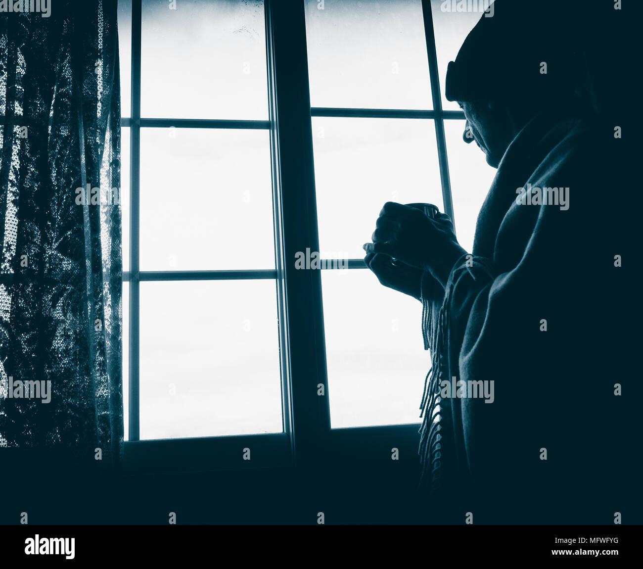 Hombre maduro celebración taza mirando por la ventana: la soledad, la salud mental, que viven solas, imagen concepto... Imagen De Stock