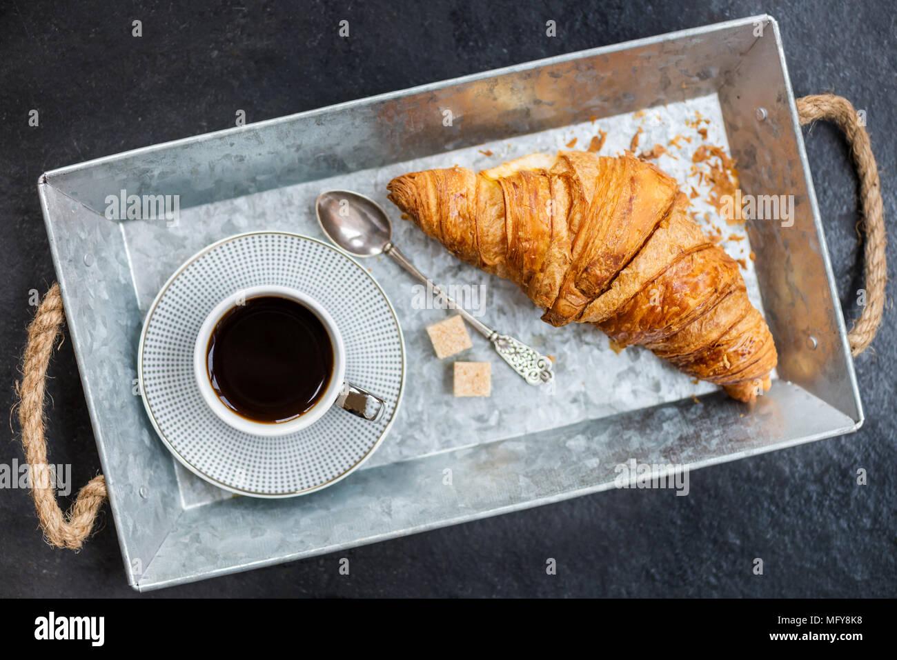 Desayuno ligero desde croissants frescos y una taza de café en la bandeja gris Foto de stock