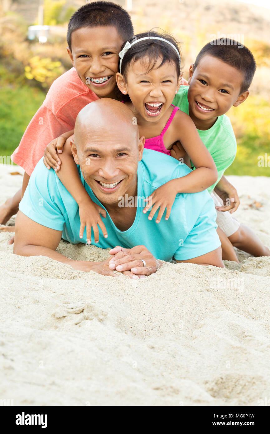 Padre jugando con sus hijos en la playa. Imagen De Stock