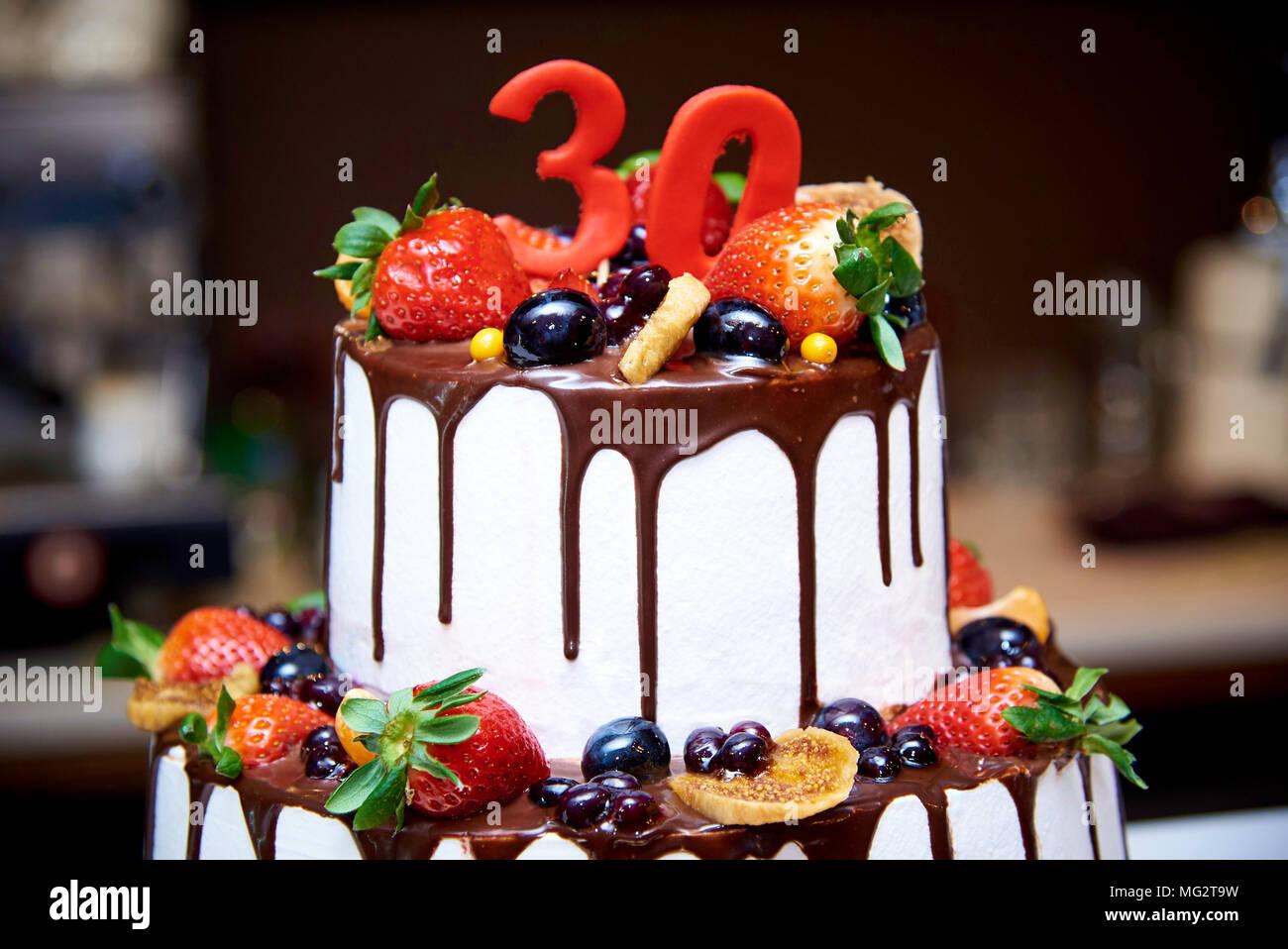Pastel blanco de dos niveles con frutas y chocolate decorada con una figura de treinta close-ups. Foto de stock
