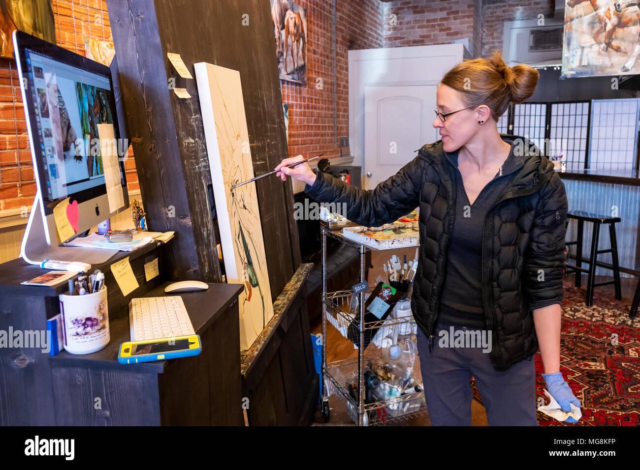 Artista Katie Maher referenciar una imagen de equipo al crear un óleo en su galería; Salida, Colorado, EE.UU. Foto de stock