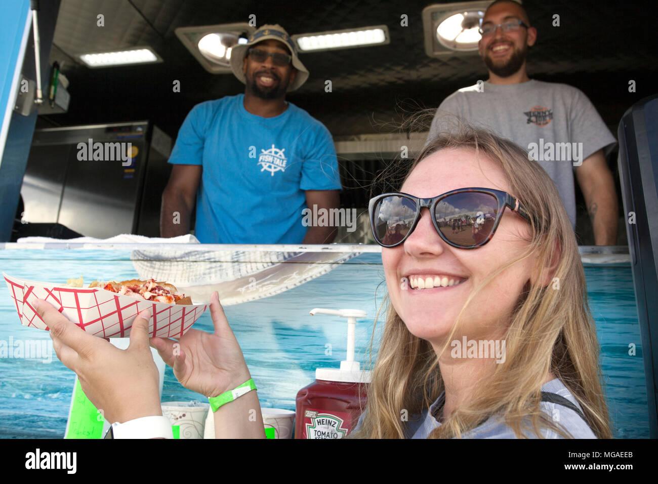 Retrato de un cliente satisfecho, feliz hembra delante de un camión de alimentos de carnaval con un basketful de aros de cebolla frita Imagen De Stock