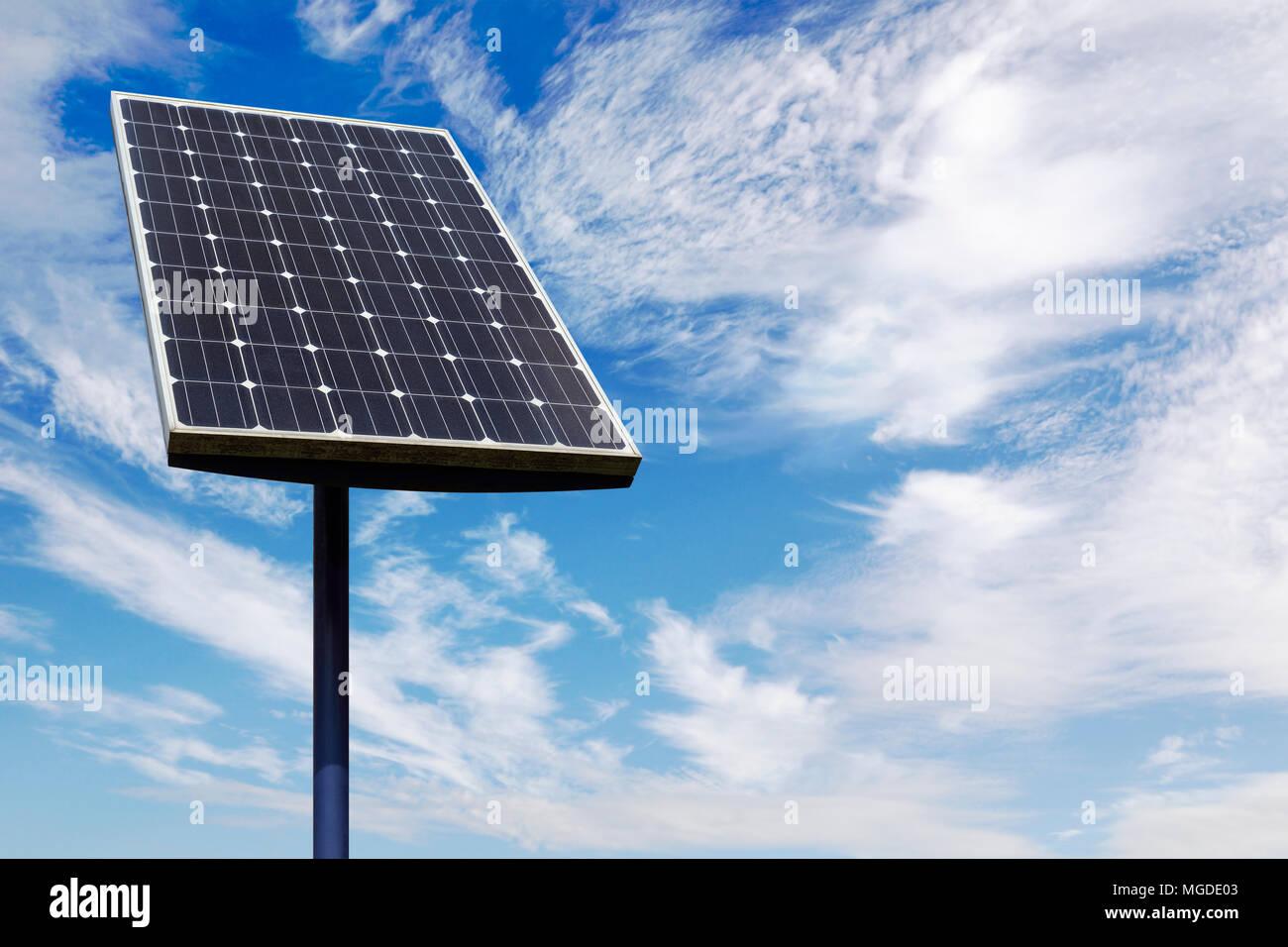 Panel Solar pequeño contra Un nublado cielo azul Imagen De Stock