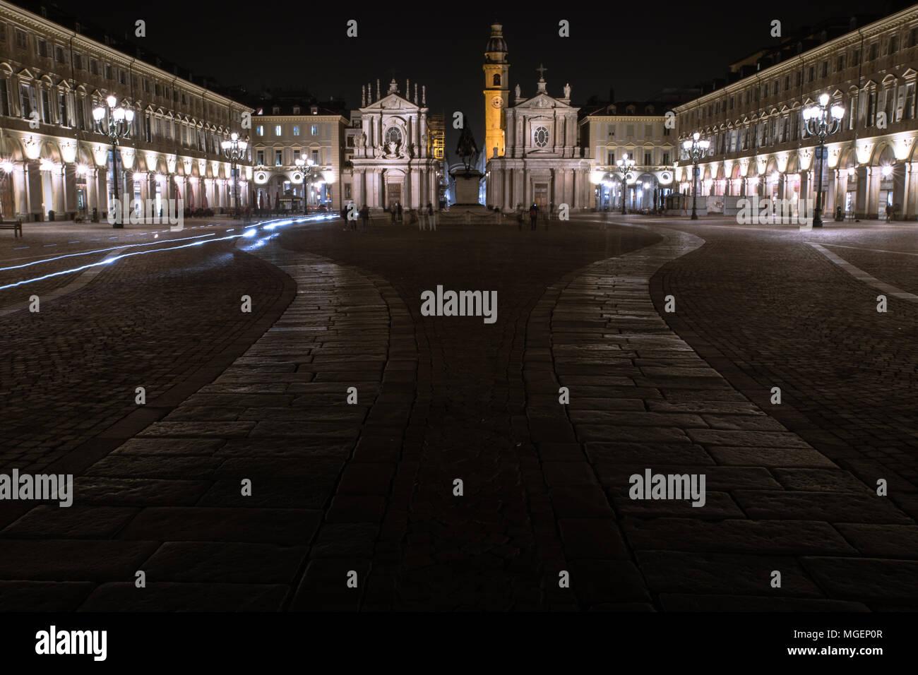 Una de las principales plazas de Turín, Piazza San Carlo, fotografiado en la noche mientras los faros de las motos whiz pasado los monumentos históricos Foto de stock