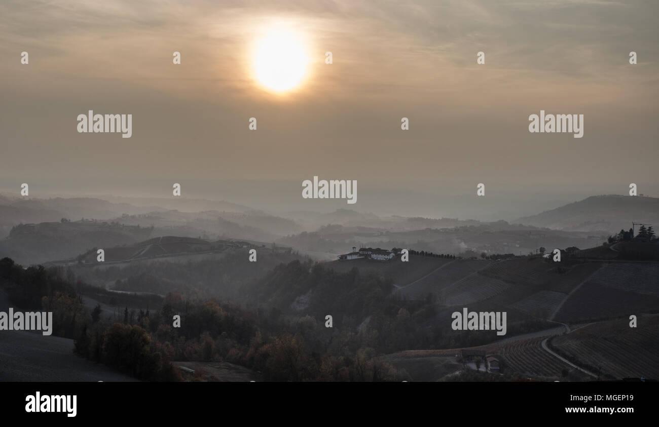 Una foto panorámica al atardecer en un día de niebla en la región de Langhe, en el Piamonte, una zona cerca de Turín, famosa por sus vinos y viñedos. Foto de stock