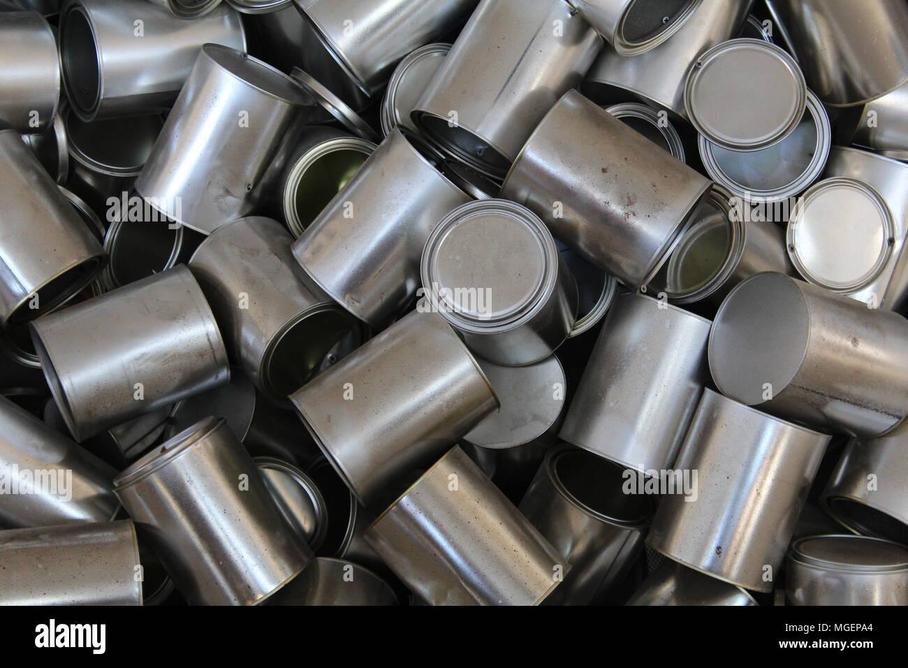 Acumulación de latas de estaño gris apilados unos encima de otros en una manera muy desordenado Foto de stock