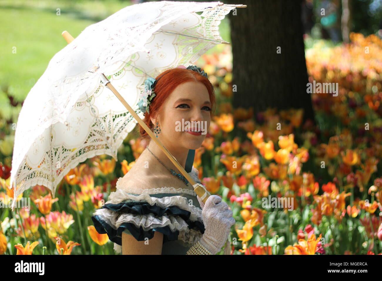 Una mujer con pelo rojo y blanco paraguas para protegerse del sol se relaja en un campo de tulipanes rojos y amarillos Foto de stock