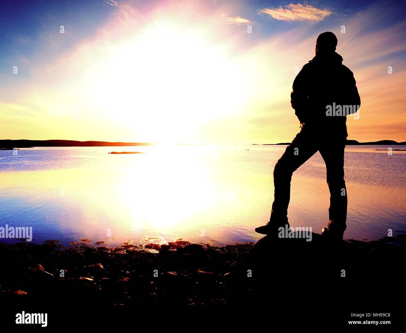Silueta de un hombre en ropa de calle en acantilado rocoso sobre el mar. Hikerthinking durante la puesta de sol en el fondo. Concepto de viaje lejos. Imagen De Stock