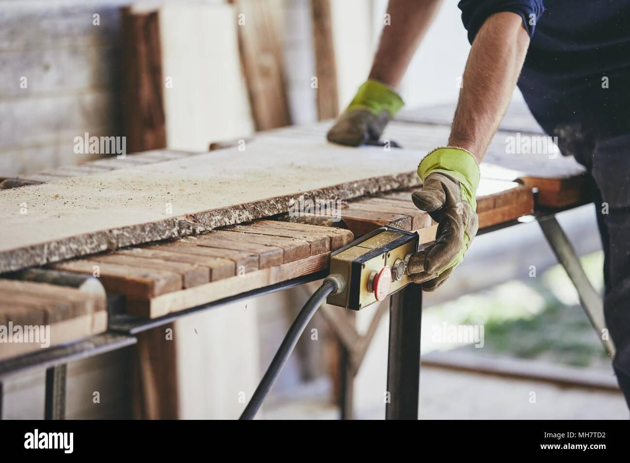Hombre trabajando en el aserradero. Las manos del trabajador con guante de protección. Imagen De Stock