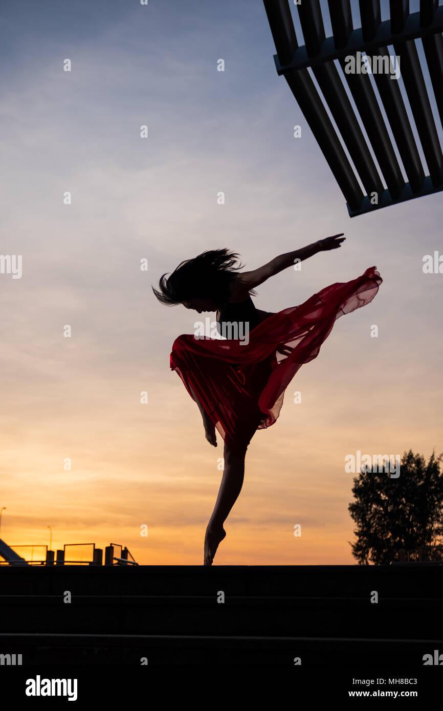 El Bailarín elegante mujer bailando ballet en la ciudad de Singapur al amanecer. Imagen De Stock