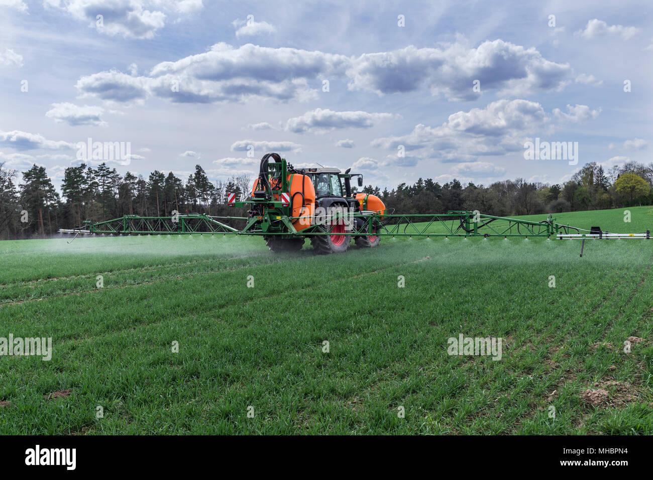 Pulverizador de alta tecnología moderna en uso en un campo de trigo, germinando Franken, Baviera, Alemania Imagen De Stock