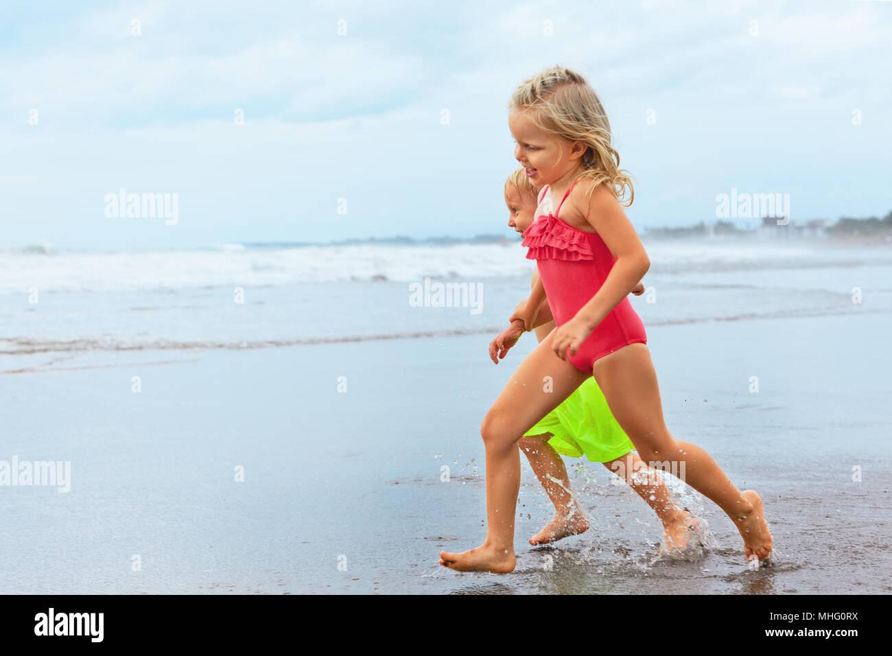 Felices los Niños descalzos divertirse en Sunset Beach Walk. Correr por la piscina de agua de mar a lo largo de surf y de salto. El viaje de la familia el estilo de vida, actividades de natación Imagen De Stock