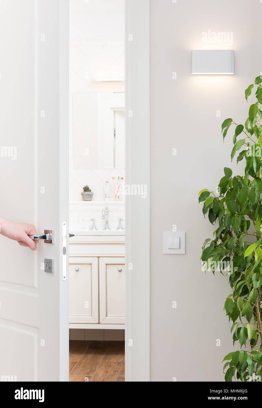 Abra la puerta del baño. Moderno y luminoso interior con elementos decorativos. Hombre mano en el asa cromada Foto de stock